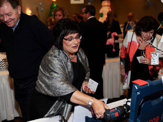Teresa Folino has her eye on a cordless drill as her friend Ed Funke looks on with a big smile.