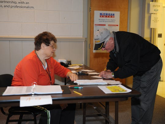 South Lyon election worker Kay Swanson checks in George