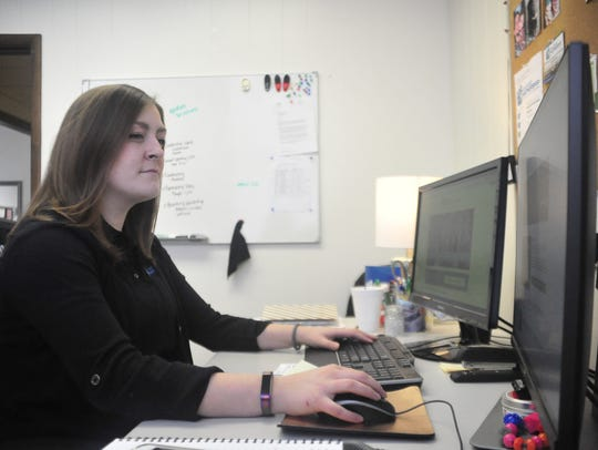 Hannah Jacobs looks over the new Crawford Partnership website in her office.