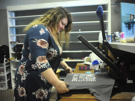 Kaela Downey sets a shirt on the heat press inside