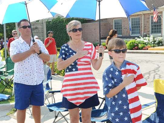 """The Squires family from Plymouth listens to the """"Star Spangled Banner."""""""