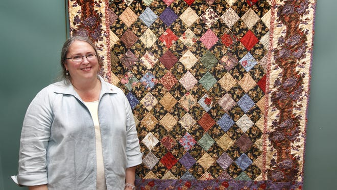 Dixie Webb poses with one of her quilts in this 2011 photo.