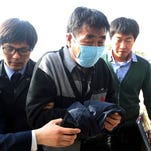 Lee Joon-seok, center, the captain of the sunken ferry boat Sewol in the water off the southern coast, arrives April 19 at the headquarters of a joint investigation team of prosecutors and police in Mokpo, south of Seoul, South Korea.