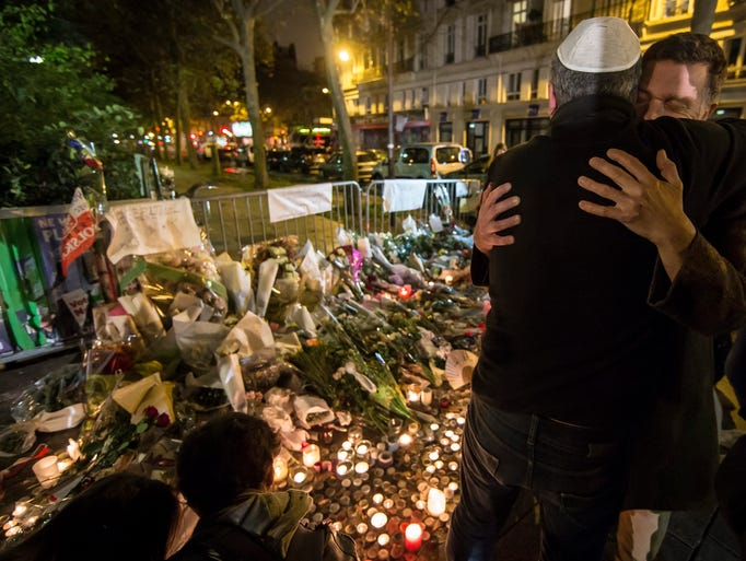 Two men hug at a vigil site near the Bataclan theater