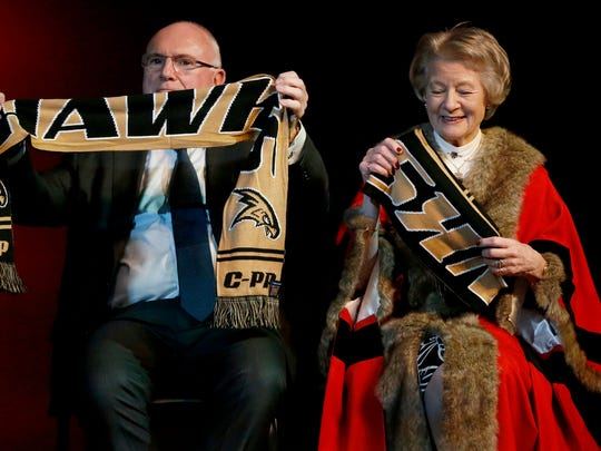 London's New Year's Day Parade and Festival co-founder Robert Bone and Westminster Lord Mayor Catherine Longworth unfold their Corning-Painted Post Hawks scarf gifts Monday in the high school's theater.