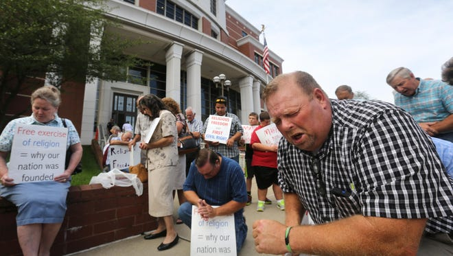 Harley Sexton of Sharkey, Kentucky, pastor of the Sharkey Freewill Baptist Church, prays along with other supporters of Rowan County clerk Kim Davis Monday morning outside the federal courthouse in Covington, Kentucky. They drove up to support Rowan County clerk Kim Davis, who is among a handful of clerks who have refused to grant licenses to any couples in order to avoid handing them out to gays and lesbians. The American Civil Liberties Union of Kentucky filed a lawsuit on behalf of four couples who were denied marriage licenses by the Rowan County clerk in the wake of the U.S. Supreme Court's historic decision legalizing same-sex marriages.