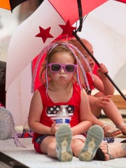 4-year-old Nicole Hicks stays cool under an umbrella on a float in Pinckney's Memorial Day parade Monday, May 28, 2018.