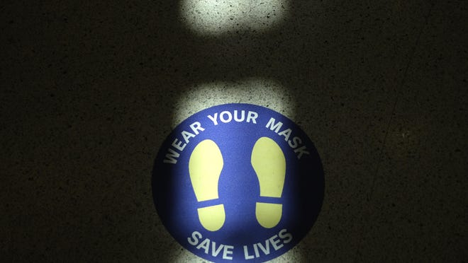 A sign advising passengers to wear masks is displayed on the floor Wednesday of Newark Liberty International Airport in Newark, New Jersey. Gov. Phil Murphy on Tuesday announced eight more states now meet the metrics under New Jersey's travel advisory. Visitors to the state from California, Georgia, Iowa, Idaho, Louisiana, Mississippi, Nevada and Tennessee should self-quarantine for two weeks. Those states join Alabama, Arkansas, Arizona, Florida, North Carolina, South Carolina, Texas and Utah, which were announced last week.