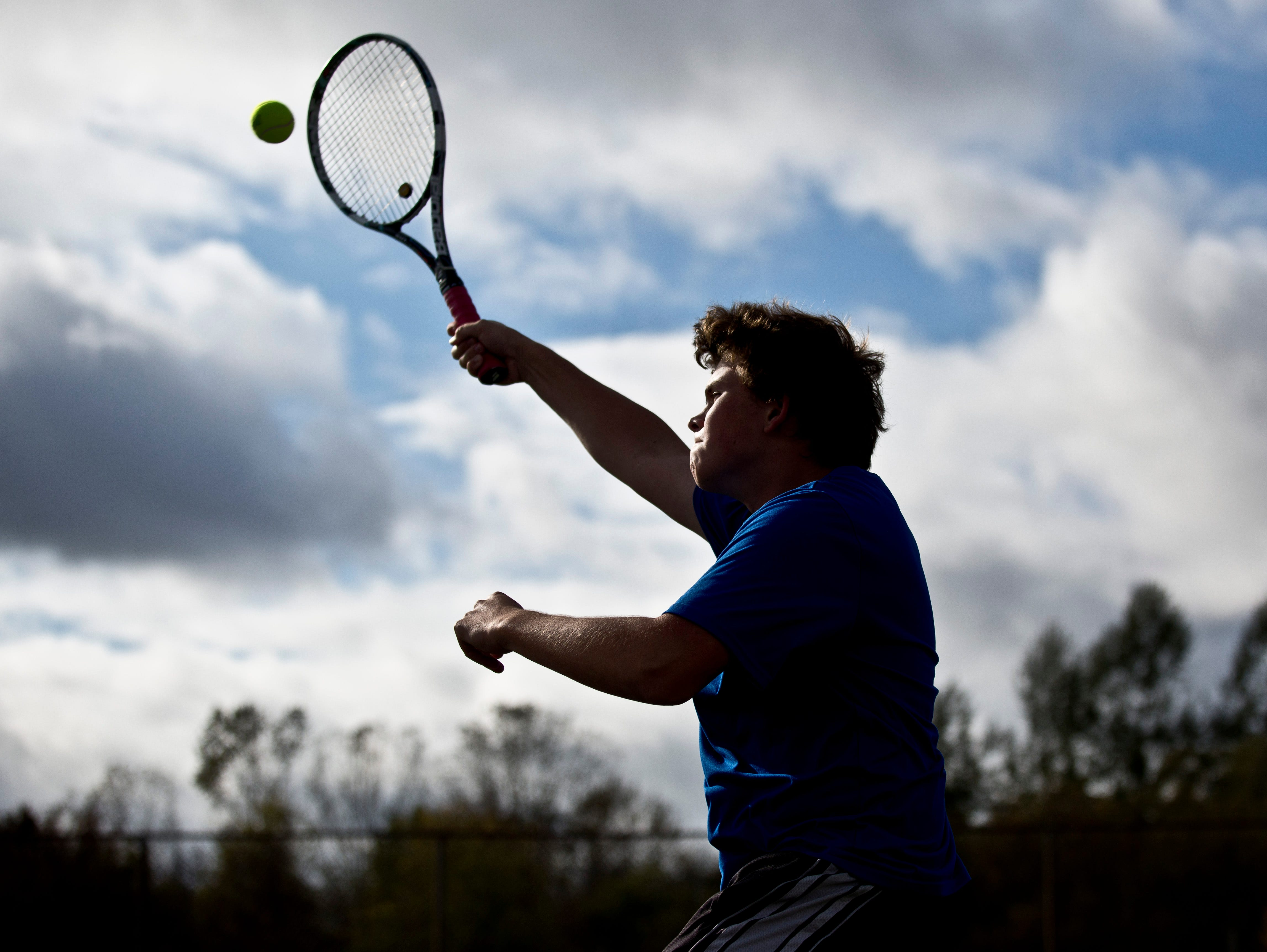 Junior Ben Offner jumps to return the ball during tennis practice Tuesday, October 13, 2015 at Armada High School.
