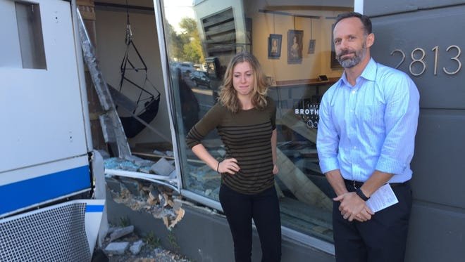 Ashley Sanfino, manager and T.J. Wilt, owner of Three Brothers Coffee, show off the window damage that occurred when an MTA bus hit the shop on Wednesday, Oct. 21, 2015.