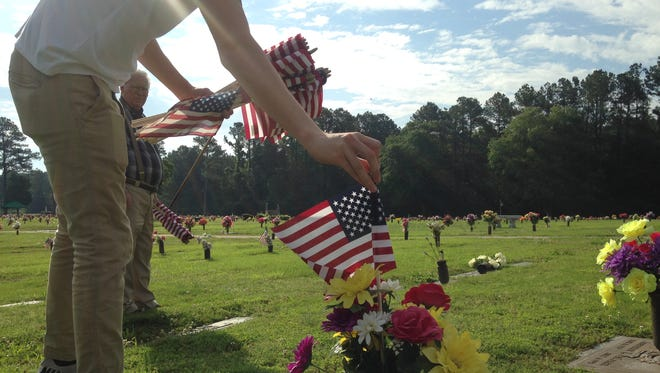 Jerry George places an American flag on a grave at Highland Memorial Gardens Saturday morning.