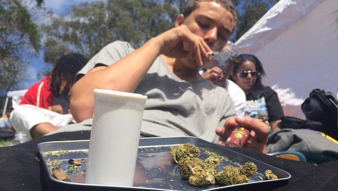 In this April 20, 2016, William Ealy smokes marijuana in Golden Gate Park as people gather at the park to smoke pot for the annual 4/20 celebration in San Francisco, Calif. A first-ever event sponsored this weekend by High Times magazine at a tribal events center near Las Vegas, Nev., will be smokeless after a U.S. attorney in Nevada warned the host Moapa Band of Paiutes that federal law applies on Indian reservations--the tribe declared that smoking, selling, trading and transporting marijuana won't be allowed