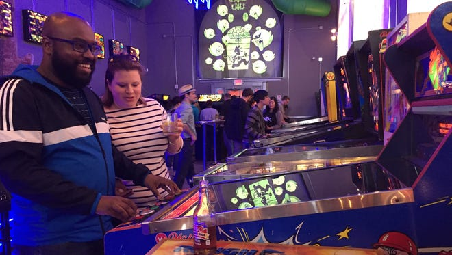 Calvin Williams, of Lansing, plays Slugfest during the soft opening at The Grid Arcade & Bar in Old Town. The bar opens on Tuesday.