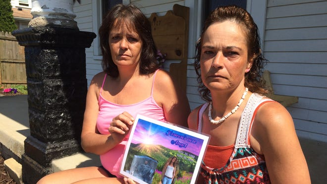"""Connie Sayre, left, and her sister Samantha Sayre hold a picture that reads """"Heavens new Angel"""" and features a picture of Connie's daughter Tiffany Sayre and a headstone purchased for Tiffany. They are fighting for tangible proof the body they buried beneath that headstone two years ago is really Tiffany."""