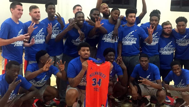 Members of MATC's basketball team, with the jersey of late teammate Will Kellerman, celebrate their victory Wednesday night over Western Technical College.