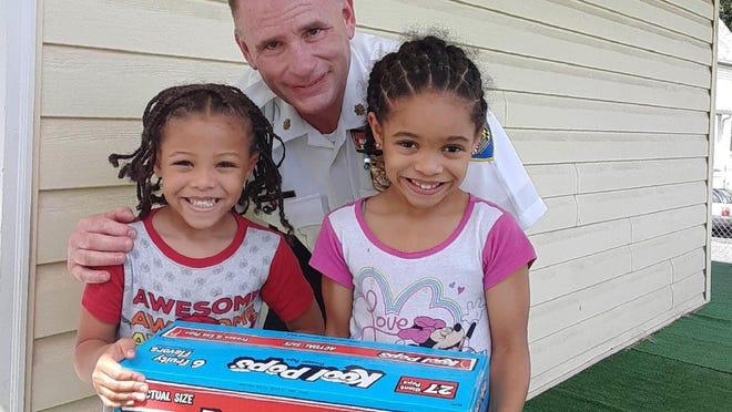 Jayden Dantzler-Clay, 5, and his sister, Amiyah Dantzler-Clay, 6, hold a box of ice pops with police Maj. Richard Gibson on July 20 at their home in Baltimore. The siblings gave a grape-flavor ice pop to the officer as he worked in their neighborhood on a hot summer day. Two days later, Gibson came back to return the favor.