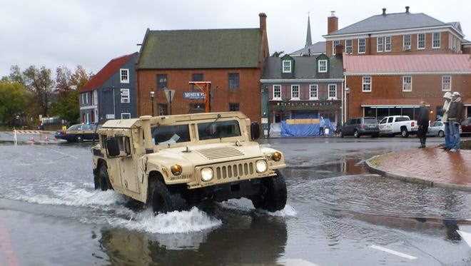 A military Humvee maneuvers through flooded streets in downtown Annapolis, Md., on Oct. 30, 2012, in the aftermath of Hurricane Sandy. Annapolis is home to the U.S. Naval Academy, which was one of the first military installations to be analyzed for climate risks.