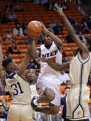 UTEP's Dominic Artis collides with a pair of FIU defenders Thursday at the Don Haskins Center.