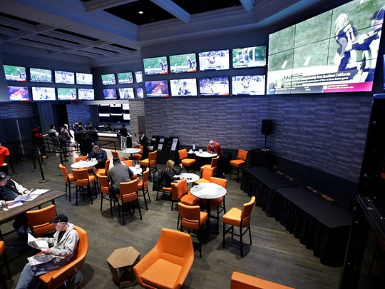 In this Monday, Jan. 28, 2019 photo, patrons visit the sports betting area of Twin River Casino in Lincoln, R.I.