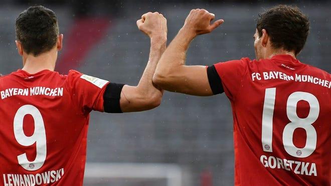Munich's Leon Goretzka celebrates scoring their first goal with Robert Lewandowski duringh the German Bundesliga soccer match between Bayern Munich and Eintracht Frankfurt in Munich, Germany, Saturday, May 23, 2020.