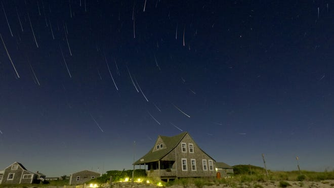 Star trails form around the north star, upper right, in a three hour time exposure over the Sandy Neck Cottage Colony. Star trails reflect the earth's rotation on its axis.