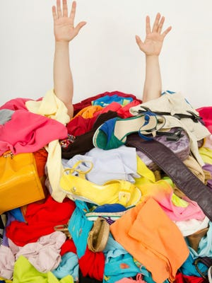 Man buried under an untidy cluttered woman wardrobe.