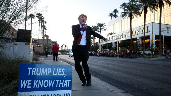Gil Mobley is dressed as Republican presidential candidate Donald Trump as he protests against the candidate outside the Trump International Hotel Tuesday, Feb. 23, 2016, in Las Vegas. (AP Photo/Jae C. Hong)