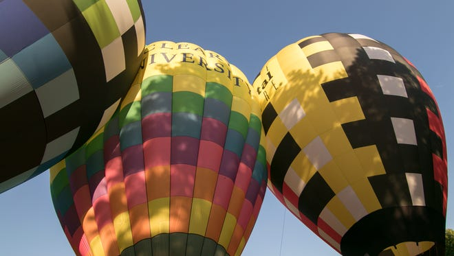 With strong breezes keeping balloons tethered, the Sullair balloon, left, Cleary University's and Michigan Cat's balloons press against one another on a tight launch area at Howell City Park Wednesday, June 13, 2018.