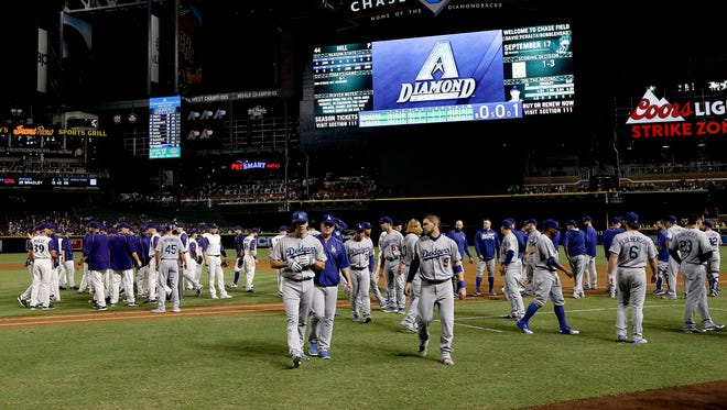 The Los Angeles Dodgers and the Arizona Diamondbacks benches walk back to their dugouts after words were exchanged during the fifth inning of a baseball game, Thursday, Sept. 15, 2016, in Phoenix.