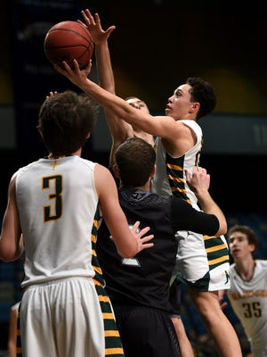 Bishop Manogue's Gabe Bansuelo (24) scores while taking on North Valleys during their basketball game at the Reno Events Center on Jan. 23, 2016.