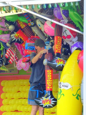 A worker hangs more prizes at a booth over the weekend.