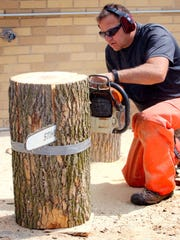 West Allis Forestry Department Arborist cuts a log into a furniture part for the West Allis Downtown Business Improvement District (BID)  Wood & Wings! event set for Sept. 16 in the Visit West Allis downtown where artists will embellish log chairs made by West Allis Forestry department staff, and vendors will offer some of the best wings in West Allis.