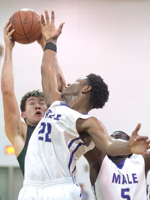 Male center-forward Noah Courtney gets a hand up to block the shot of St. X center-forward Evan Walker. In on the play is Male guard Tyren Moore, bottom right.Jan. 19, 2018