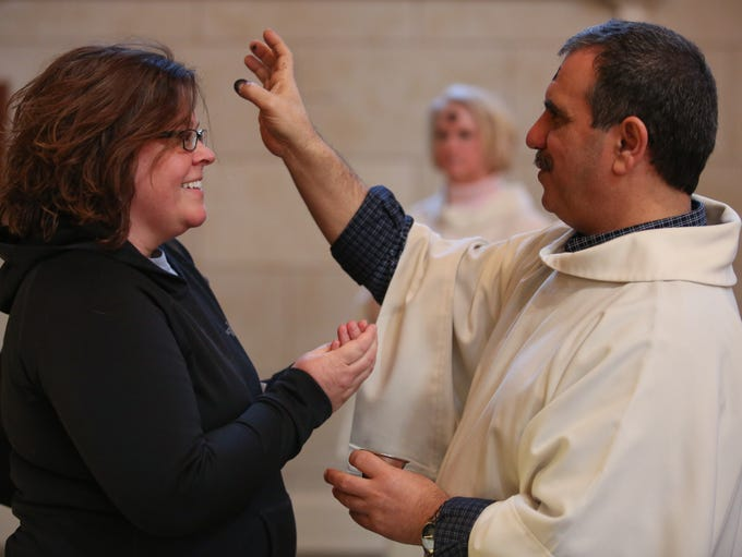 George Kaissiah, right, places ash on the head of a repenter during Ash Wednesday services at Cathedral of the Assumption. March 5, 2014