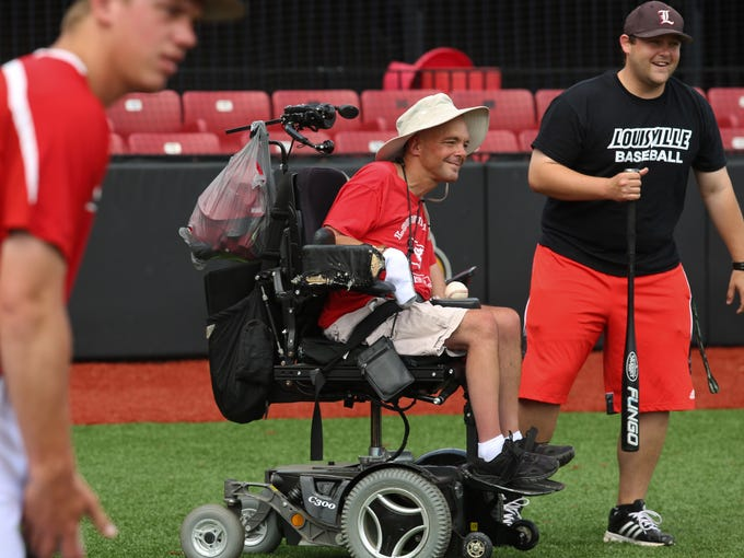 Louisville Cardinal baseball video coordinator Ryan Warkentien, from right, has a laugh with fan Michael Todd Esser, 42, diagnosed with cerebral palsy, as pitcher Jonah Philley looks on during practice Wednesday. May 28, 2014