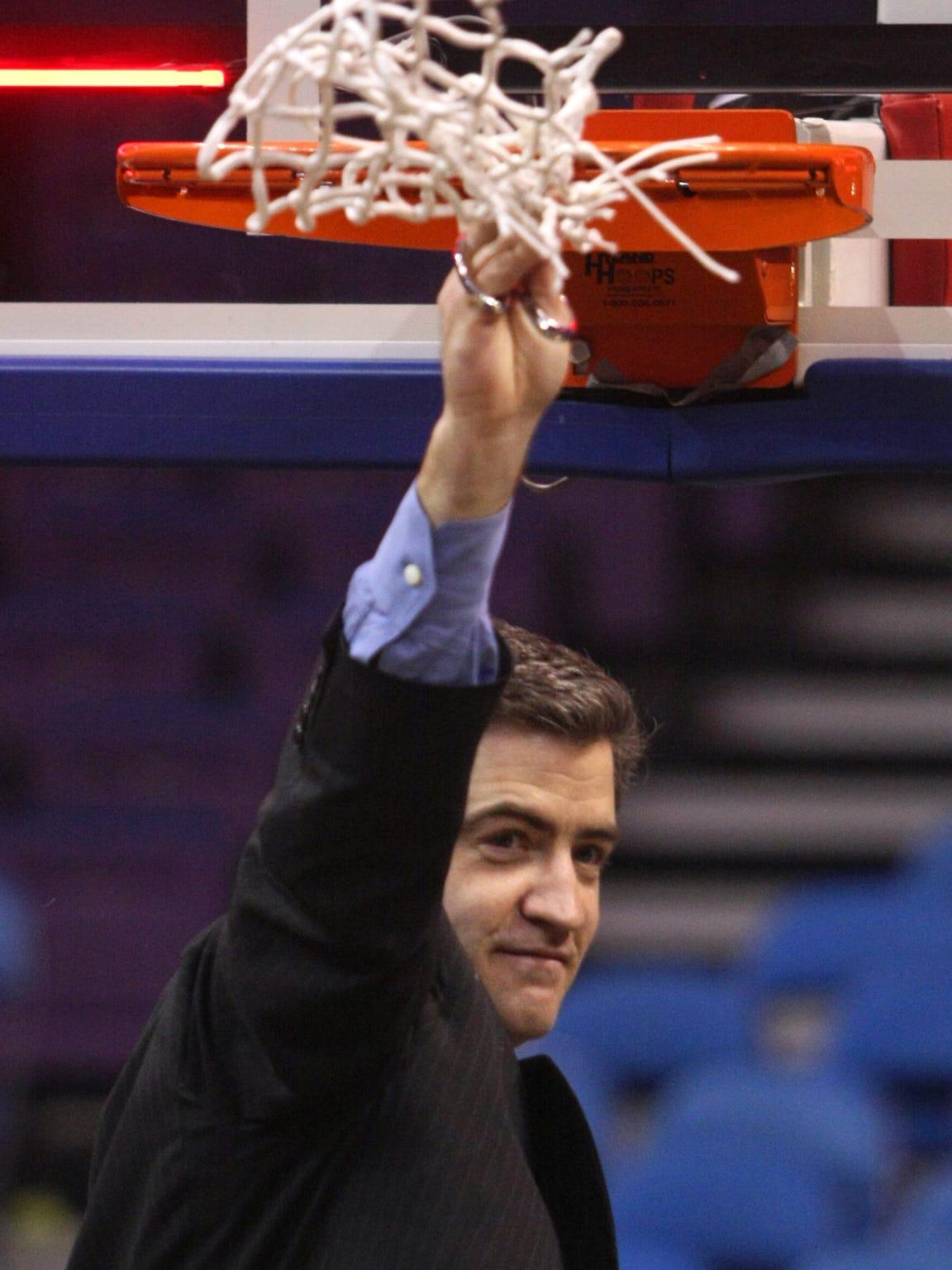Drake coach Keno Davis raises the net after cutting