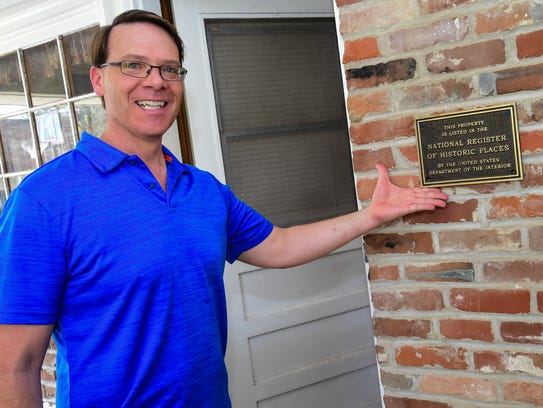 Bob Carriker points to the historic marker on his Lafayette