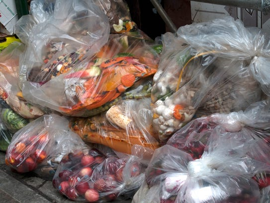 Unsold vegetables in bags are put out for garbage outside