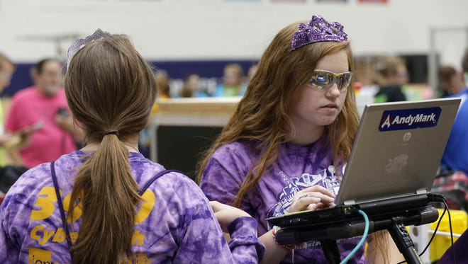 Isabelle Baker (left) and Elizabeth Bath (right), members of the Cyber Tooth team from Kokomo, make adjustments to their robots between rounds at the all-girls IndyRAGE, held on Saturday, Oct. 3, 2015, at Perry Meridian High School in Indianapolis.