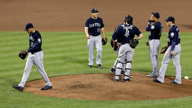 Seattle Mariners starting pitcher Taijuan Walker, left, walks off the field after being relieved in the fourth inning of a baseball game against the Baltimore Orioles, Tuesday, May 19, 2015, in Baltimore. Baltimore won 9-4.