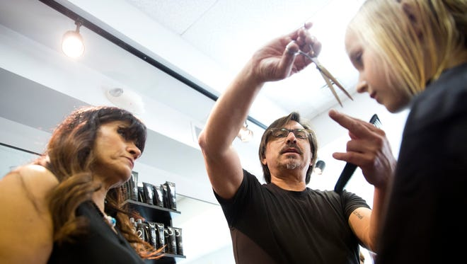 Richard Lopez, a development manager with the M Room, helps to train Michelle Sager while she cuts the hair of Emilia Kariste, 9, during a training day before the grand opening in Naples. The grand opening of the M Room, a salon whose aim and mission is directed toward men, was Saturday.