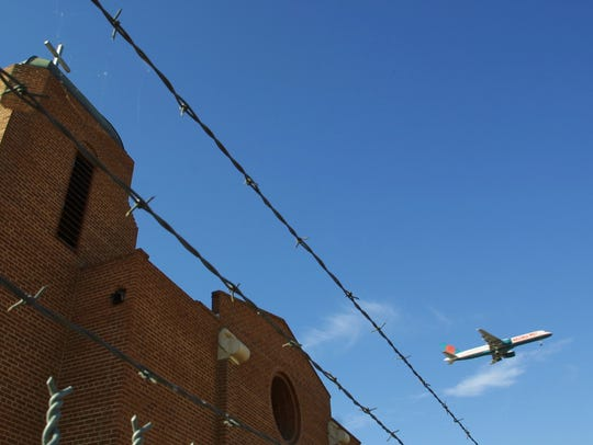 A plane flies past the shuttered Sacred Heart Church