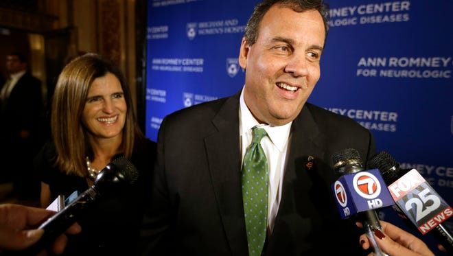 New Jersey Gov. Chris Christie, right, and his wife Mary Pat Christie, left, speak with members of the media as they arrive at the Citi Performing Arts Center Wang Theatre, Tuesday, Oct. 14, 2014, in Boston.