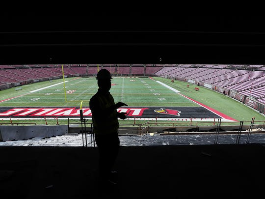 Vince Tyra is silhouetted against the midday sun hitting the field at Papa John's Cardinal Stadium as he talked about the new from the club level seats.
