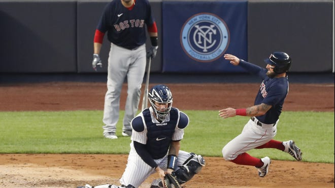 Boston's Kevin Pillar, right, scores ahead of the throw to New York catcher Gary Sanchez during the third inning of Sunday's game.