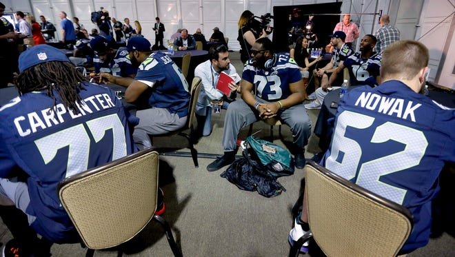 The Seahawks' Drew Nowak (62) sits at a table during a media session in Phoenix during Super Bowl week.