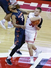 Wisconsin's Brad Davison (34) fouls Illinois' Mark Alstork during the first half.