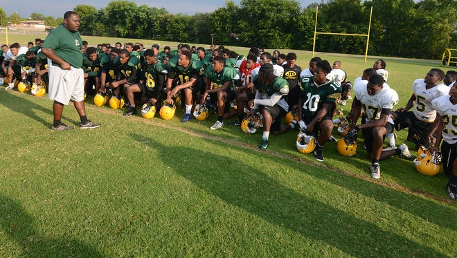 Coach Lee Carter talks with his team during Jeff Davis High School football practice at the school in Montgomery, Ala. on Friday August 8, 2014.