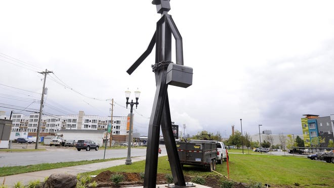 """The structural steel statue """"The Worker"""" is freshly up at Cedar and Shiawassee streets in Lansing. . The 22-foot-tall, 2,000-pound sculpture is a tribute to the blue-collar history of the area and celebrates the men and women who built the city, according to Pat Gillespie of the Gillespie Group."""