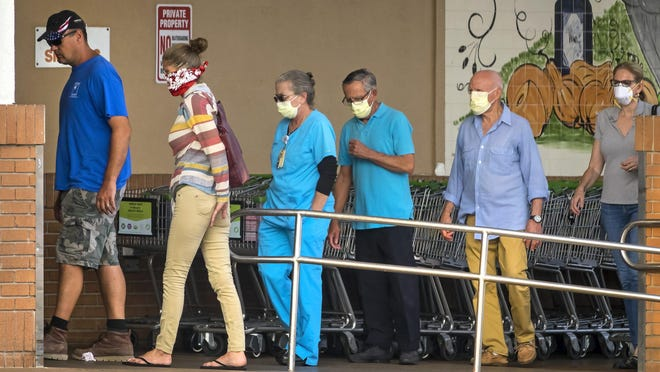 People, masked and unmasked, enter Publix on Southern Boulevard in West Palm Beach as it opens on April 13.  LANNIS WATERS/palmbeachpost.com]